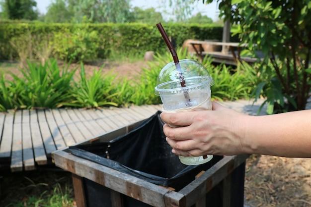 Main mettre un verre en plastique vide avec de la paille dans un bac en bois dans le parc. Photo Premium