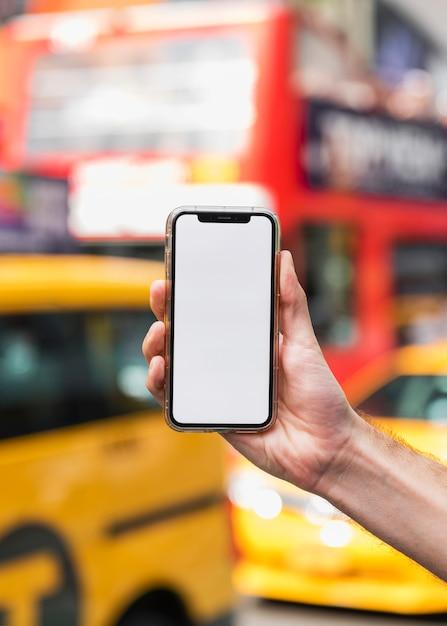 Main Avec Mobile Sur Fond Flou Photo gratuit