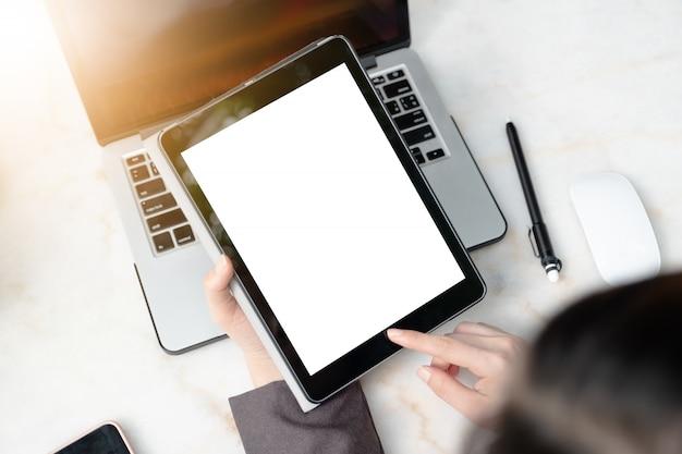 Main montrant un écran vide de tablette numérique sur le bureau Photo Premium