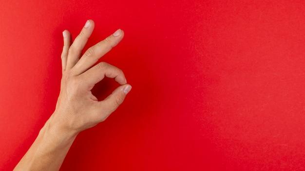 Main montrant le signe ok sur fond rouge Photo gratuit