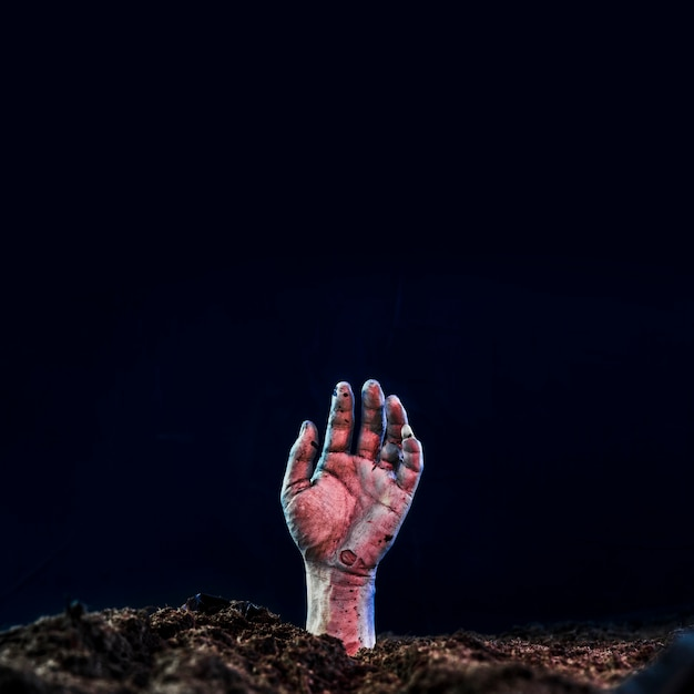 Main morte saillant du sol Photo gratuit