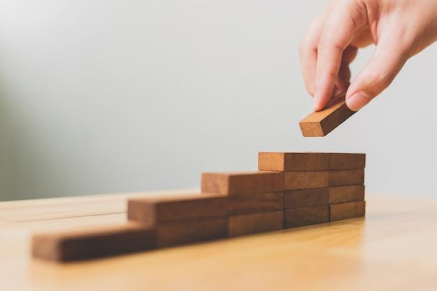 Main organisant l'empilement de blocs de bois comme marche d'escalier Photo Premium