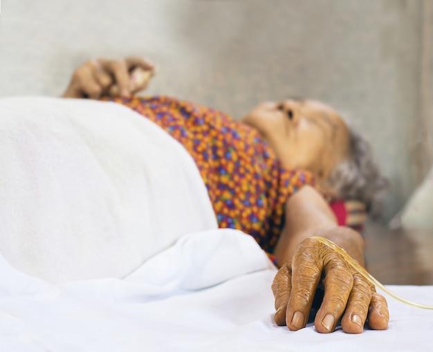 Main patients âgés à l'hôpital avec une solution saline par voie intraveineuse Photo Premium