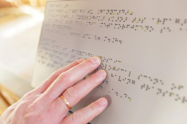 Main d'une personne aveugle lisant un texte en braille touchant le relief. Photo Premium