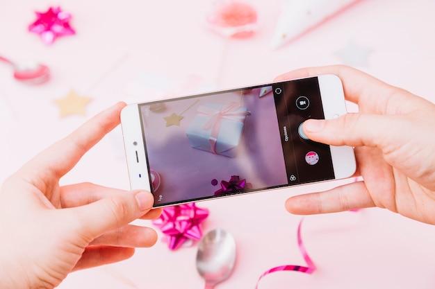 Main d'une personne capturant une photo de la fête d'anniversaire sur smartphone Photo gratuit