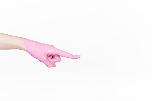 Main de la personne avec un doigt pointé peinture rose sur fond blanc Photo gratuit