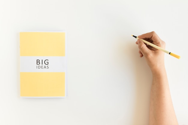 Main d'une personne écrivant sur le fond avec le journal des grandes idées Photo gratuit