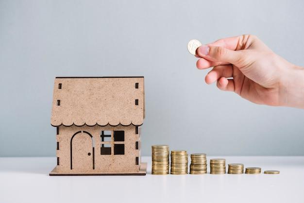 La main d'une personne empilant des pièces près du modèle de la maison Photo gratuit
