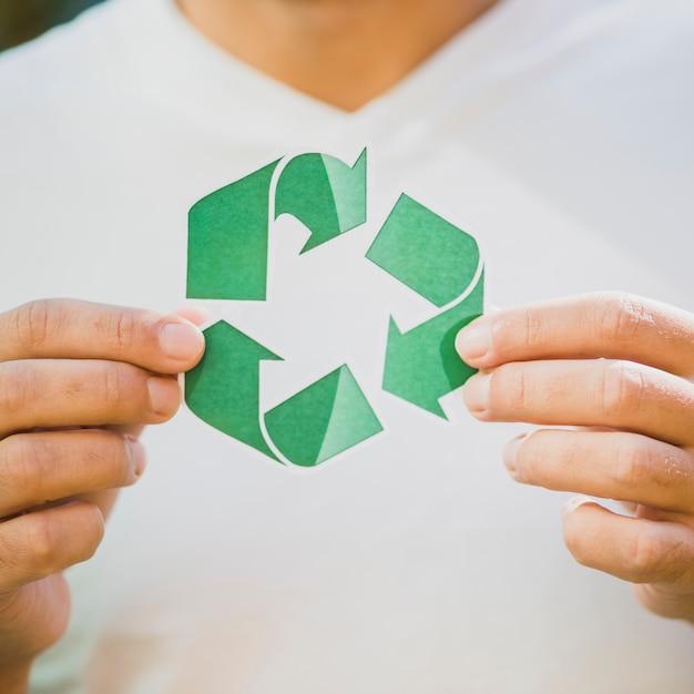 La main d'une personne montrant une icône de recyclage Photo gratuit