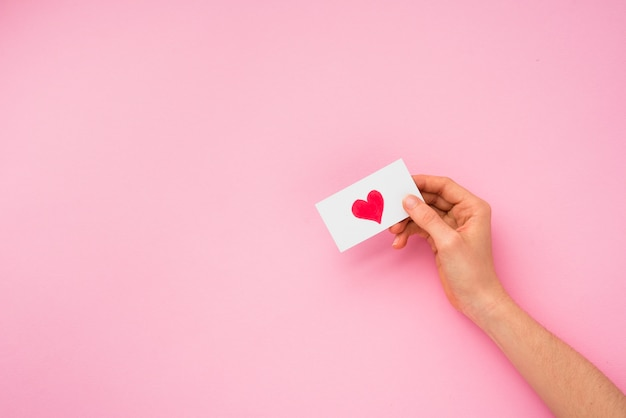 Main personne tenant papier avec image de coeur Photo gratuit