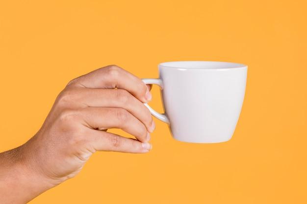 Main de la personne tenant une tasse de café sur un fond coloré Photo gratuit