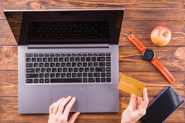 Main de la personne utilisant une carte d'or pour faire des achats en ligne avec un ordinateur portable sur une table en bois Photo gratuit