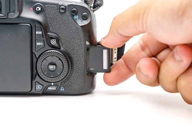 Main de photographe tenant carte mémoire sd insérer un appareil photo reflex numérique moderne Photo Premium