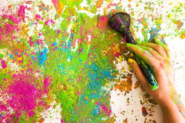 Main avec pinceau sur des couleurs vives et sèches Photo gratuit