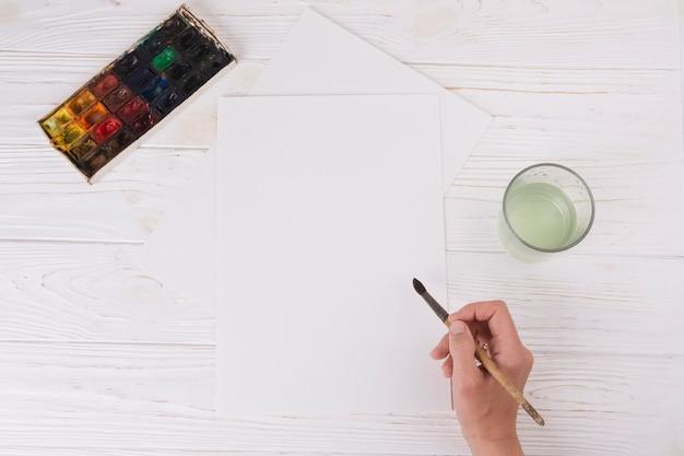 Main Avec Pinceau Près De Papier, Verre Et Set D'aquarelles Photo gratuit
