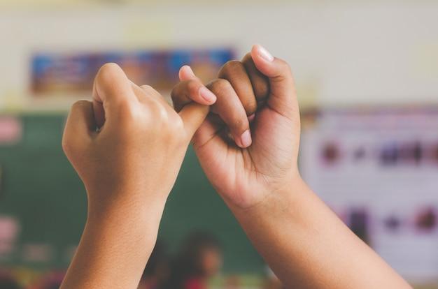 Main à pinky jure, heureux couple ou amitié tenant par la main ensemble pour toujours amour concept. Photo Premium