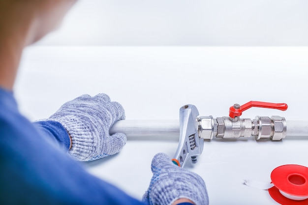 Main de plombier réparant une fuite de tuyau d'évier avec une clé à molette. Photo Premium