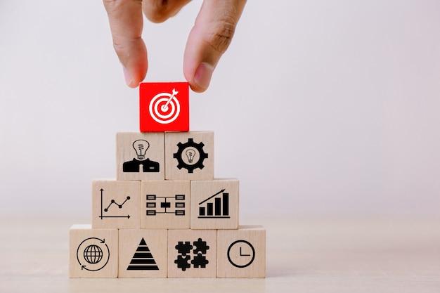 Main plus près des mains d'hommes d'affaires, empiler des blocs de bois en marches Photo Premium