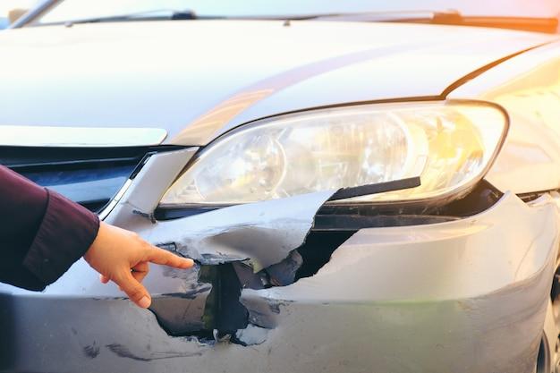 Main pointée vers la face avant de la voiture accidentée. accident de voiture accidenté automobiles endommagées Photo Premium
