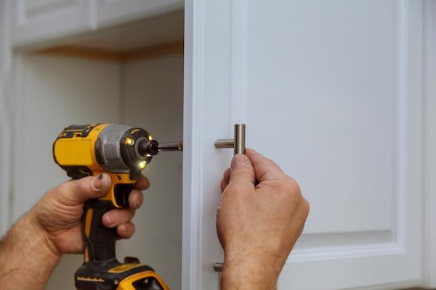 Main sur la porte d'installation de la poignée dans l'armoire de cuisine avec un tournevis Photo Premium