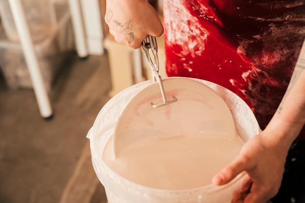 Main de potier insérant la plaque dans le seau à peinture avec une pince Photo gratuit