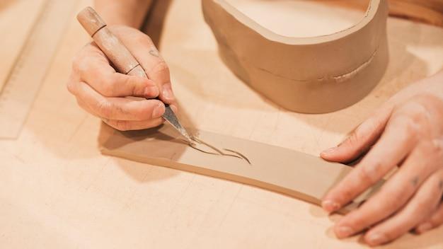 Main de potier qualifié gravant sur de l'argile avec des outils tranchants Photo gratuit