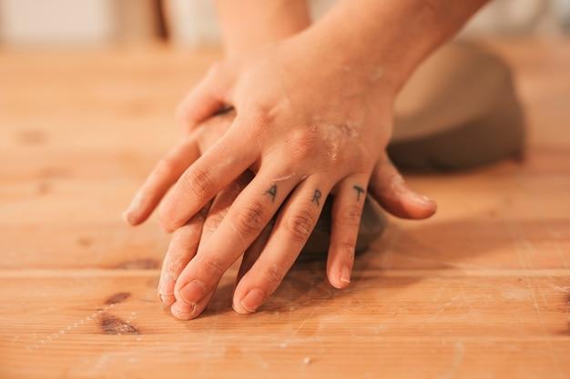 Main de potier en train de pétrir l'argile sur une surface en bois Photo gratuit