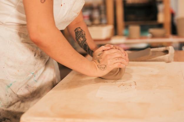 Main de potier en train de pétrir l'argile sur une table Photo gratuit