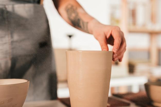 La main de potter tenant le vase en terre cuite Photo gratuit