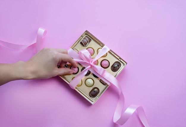 Main Prenant Un Chocolat De Boîte De Pralines Avec Noeud Rose Sur Fond Rose Photo Premium