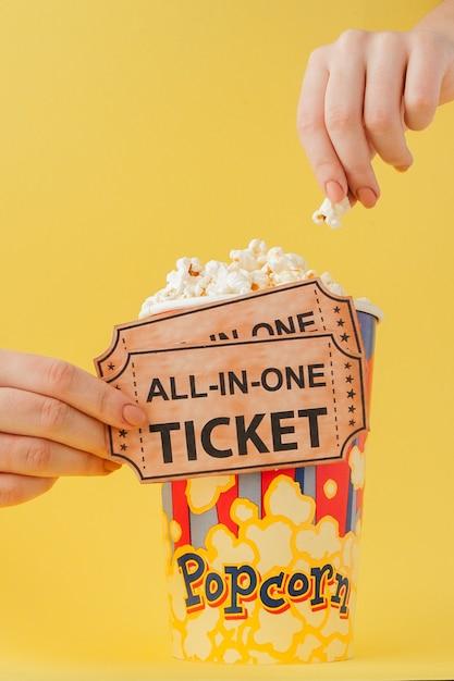 Main prend un billets de cinéma et pop-corn d'un gobelet en papier sur un jaune. femme mange du pop-corn. cinéma . lay plat. fond Photo Premium