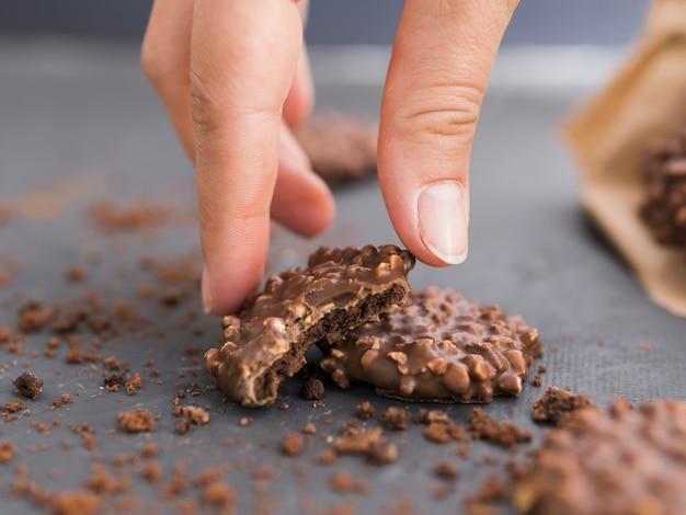 Main, prendre, biscuit chocolat, pincé, de, table Photo gratuit