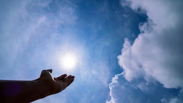Main priant pour la bénédiction de dieu sur le soleil et les nuages, concept de religion chrétienne Photo Premium