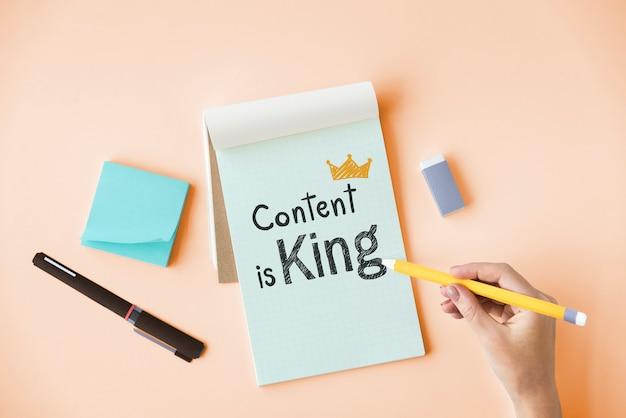 Main qui écrit le contenu est roi sur un bloc-notes Photo Premium