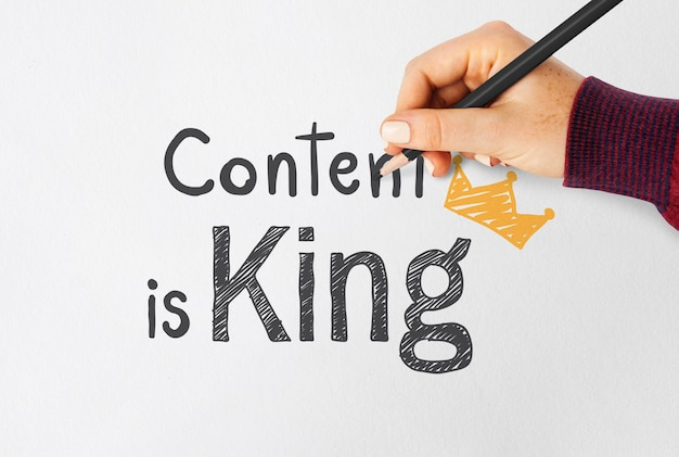 Main qui écrit le contenu est roi sur un papier Photo Premium