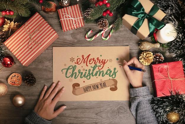 Main qui écrit le texte joyeux noël de carte de voeux avec la décoration de noël sur la table en bois. Photo Premium