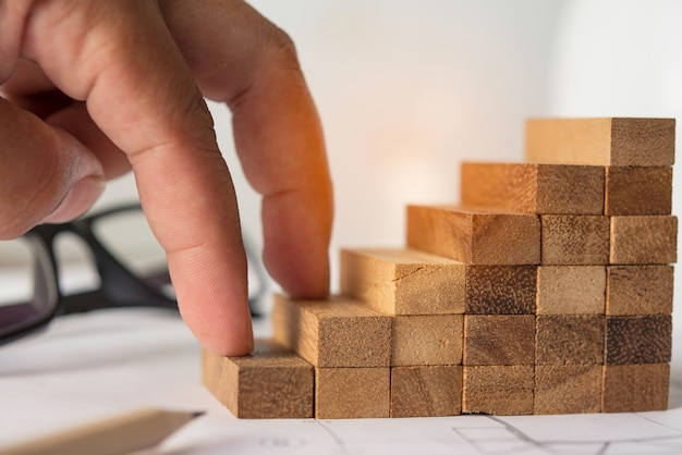 Une main qui grimpe sur un bloc de bois - un concept d'effort. Photo Premium