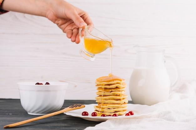 Une main qui verse du miel sur les délicieux pancakes sur une table en bois Photo gratuit