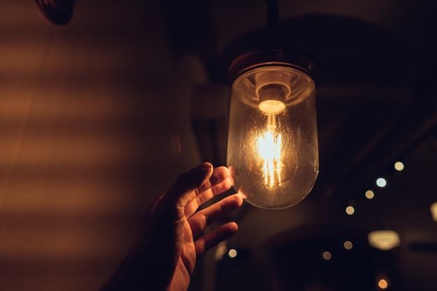 Main recherchant une ampoule vintage. Photo gratuit