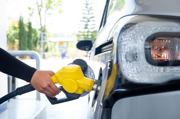 Main remplissant la voiture avec du carburant à la station d'essence Photo Premium