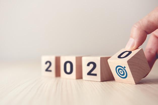Main, retournez sur les cubes de bois en bois avec le nouvel an 2020 et le concept d'icône de but. Photo Premium
