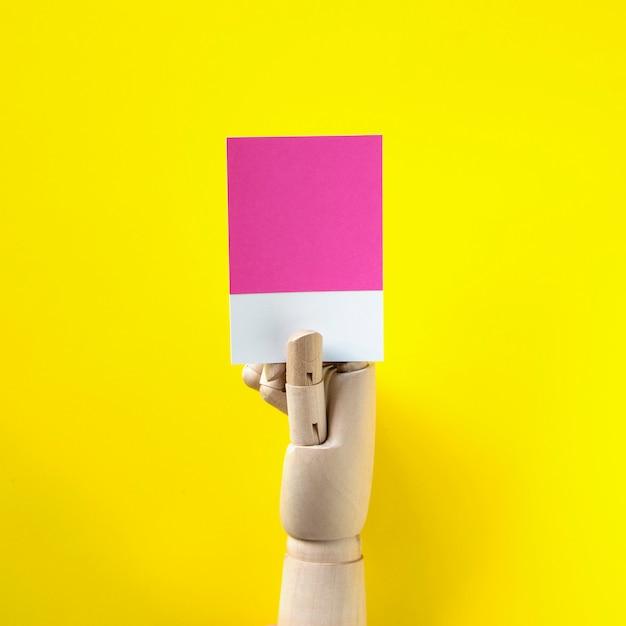 Main de robot tenant un papier vierge Photo gratuit