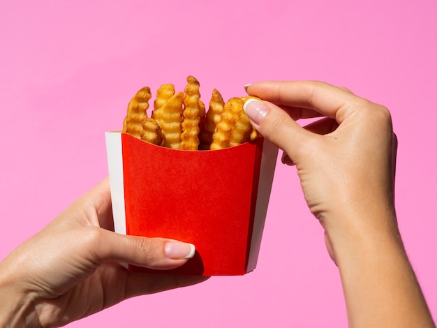 Main saisissant des frites américaines avec un fond rose Photo gratuit