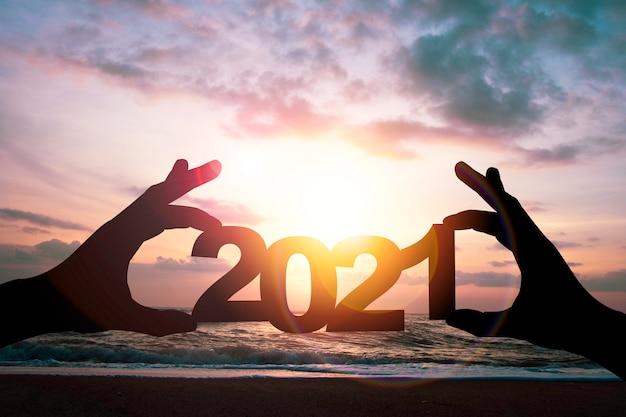 Main De Silhouette Tenant Le Numéro 2021 Sur Paysage Marin Avec Ciel De Nuages Et Lever Du Soleil. C'est Le Symbole Du Début Et De La Bonne Année 2021. Photo Premium