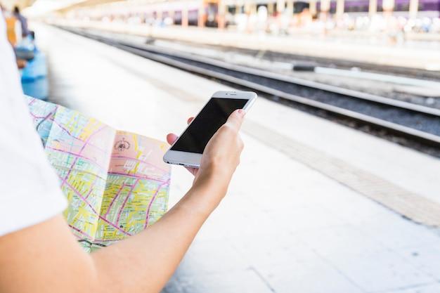 Main avec smartphone et carte Photo gratuit