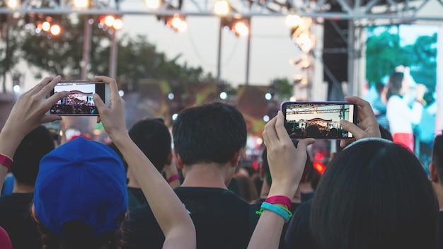 Main avec un smartphone enregistre un festival de musique en direct, prenant une photo de la scène de concert Photo Premium