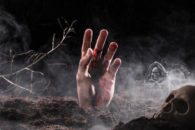 Main sortant du sol dans le brouillard Photo gratuit