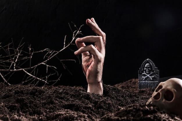 Main sortant du sol près du crâne Photo gratuit
