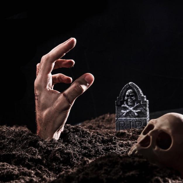 Main sortant du sol près de la pierre tombale Photo gratuit