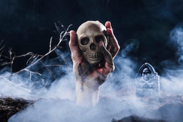 Main sortant du sol et tenant le crâne Photo gratuit